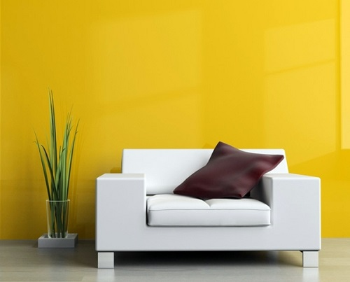 white couch next to a yellow wall