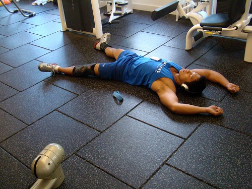 man lying on the floor of a gym