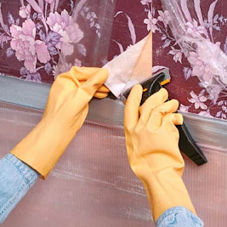 A lady waering a yellow plastic gloves and removing the floral wallpaper