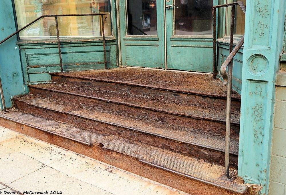 rusty steel stairs in a mint colored post