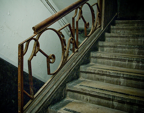 old dusty stairs with rusty metal holder