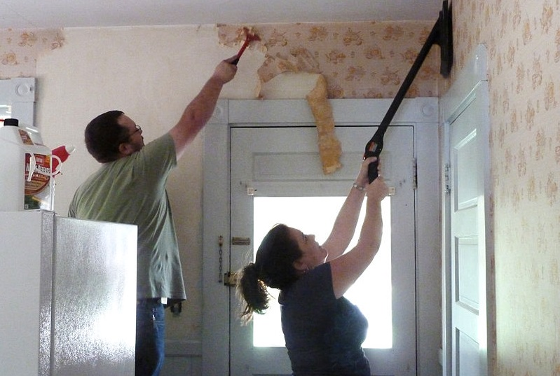a man and a lady detaching the wallpaper inside their home using wallpaper removal.