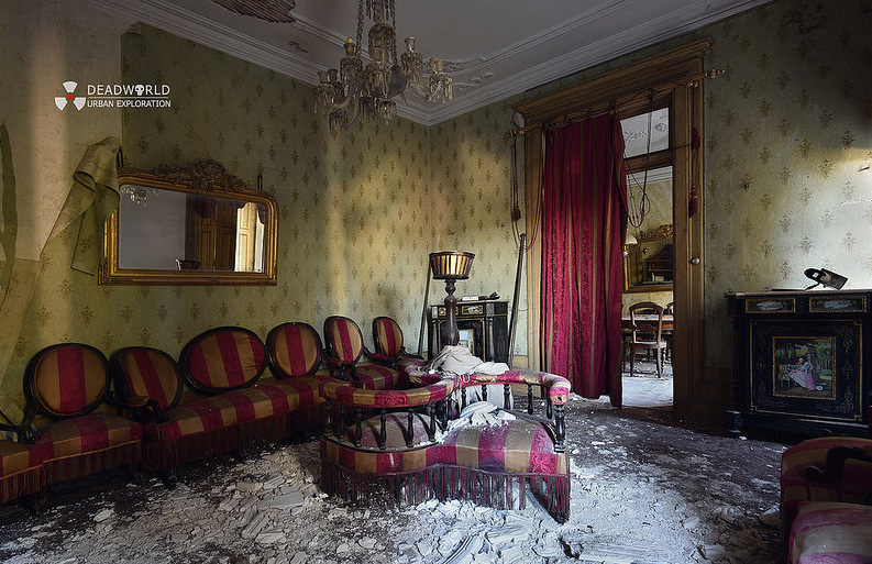 a messy old house with foam sofa sets and a cream accent wallpaper