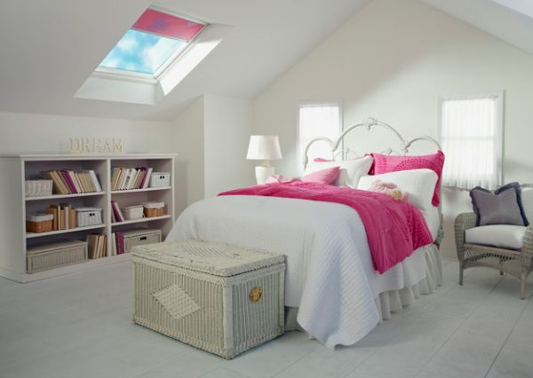 small bedroom in white and pink accent and a book shelf inside and a piece of lampshade