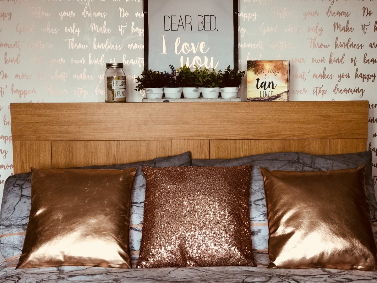 bedroom in brown accent and wood head board and shimmering tropical pillows