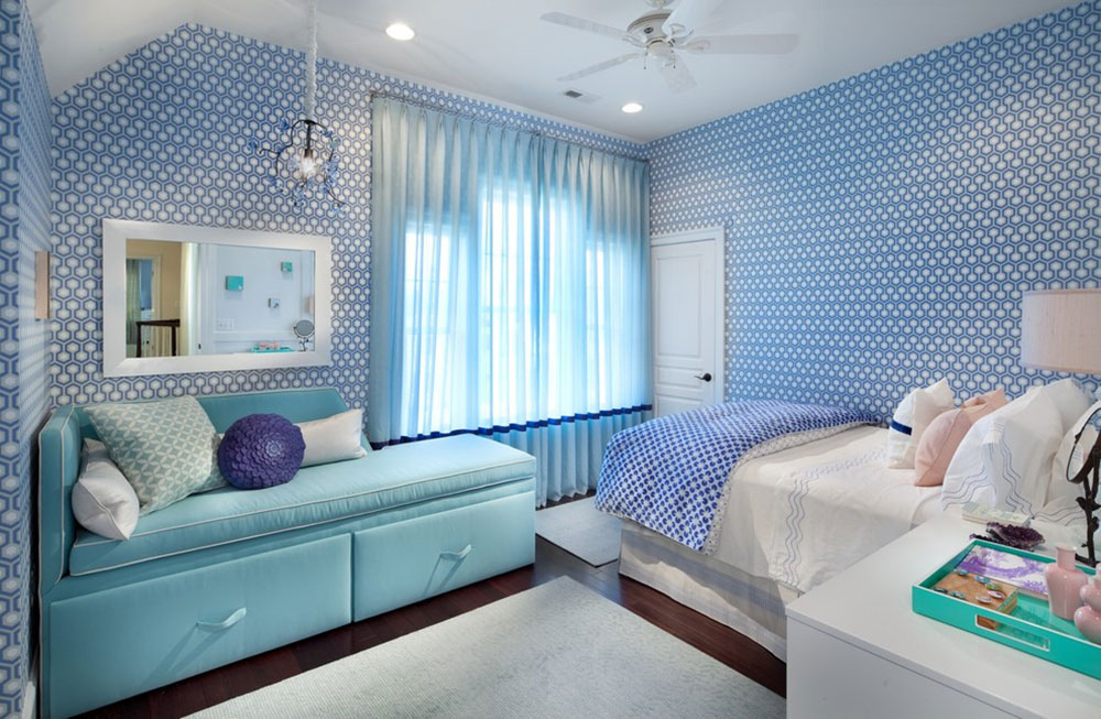 a cute small bedroom with a blue wall paper and a sofa with blue accent