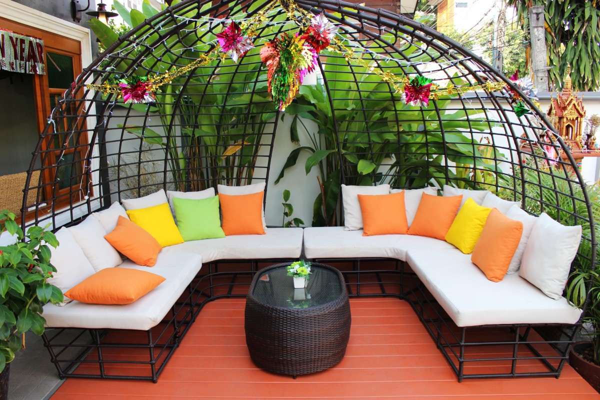 a set of sofa at the backyard together with colorful tropical pillows and a table as a center piece