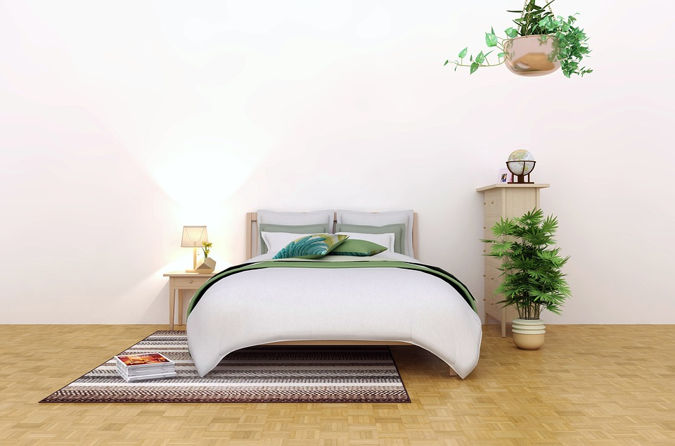 bedroom in white accent with huge bed and a pots of green plants inside.