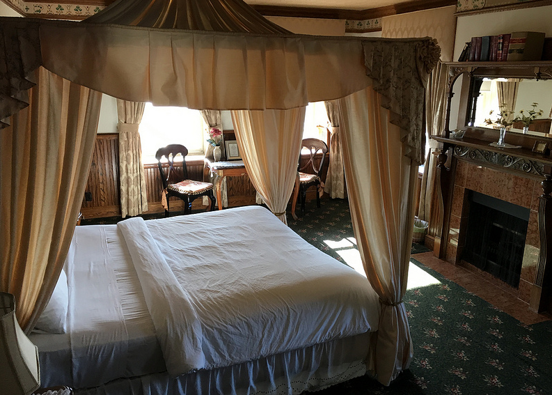bedroom with queen sized bed with curtain above  the bed.
