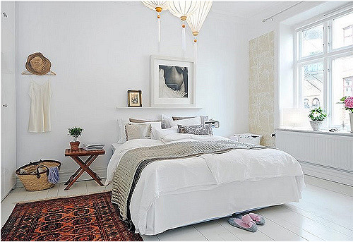 small room with a queen sized bed in a white accent with an wall frame and hat decor and a wood table.