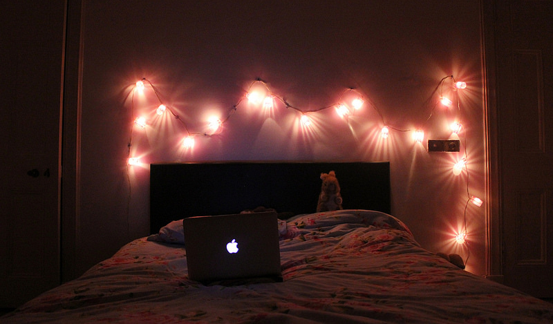bedroom in a dim accent together with fairy lights above head board.