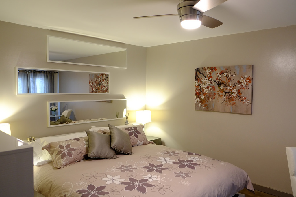 small bedroom in a very classy and smooth accent with the wall floral paint and a bed covered by a floral sheet
