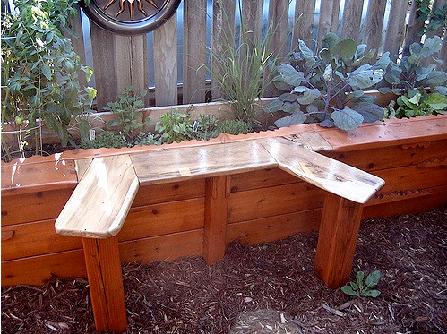 a backyard with a corner seating part made by a wood